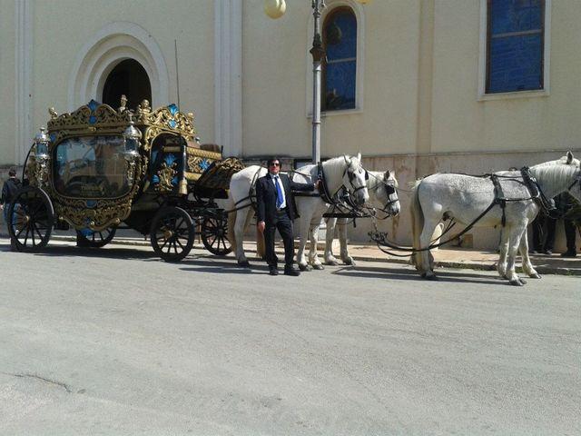 una carrozza dorata trainata da dei cavalli di di fronte a una chiesa e un uomo in piedi