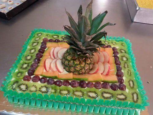 una torta rettangolare con kiwi,ciliegie,mele e un ananas al centro