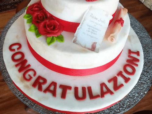 una torta di glassa bianca con rose rosse e la scritta congratulazioni