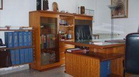 un ufficio con una scrivania in legno e due sedie