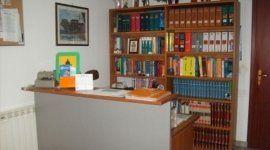 una scrivania e dietro una libreria
