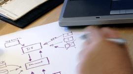 una mano con una penna,un foglio con uno schema e un portatile