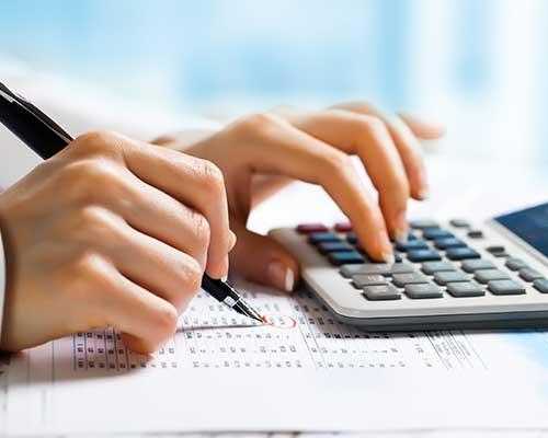 una mano che usa una calcolatrice e l'altra che scrive
