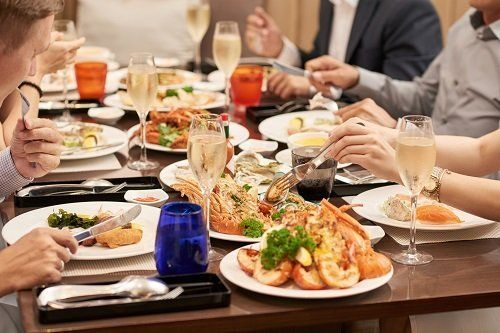 delle persone al tavolo con dei piatti a base di pesce
