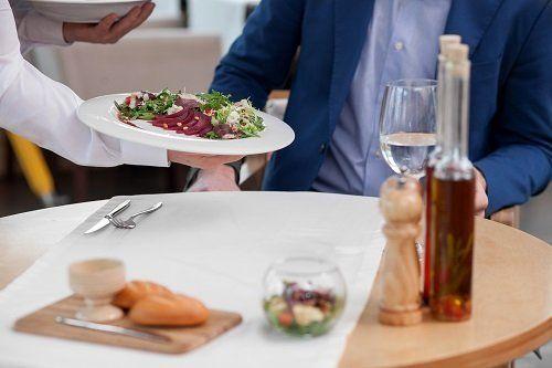 un uomo seduto al tavolo e un cameriere che serve un piatto di insalata