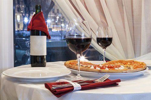 un tavolo con una pizza, una bottiglia di vino e delle posate