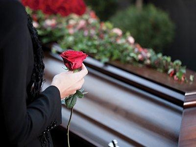 Donna tiene un fiore al funerale a Grosseto