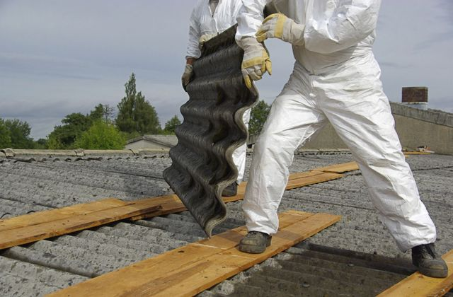 Experts in asbestos inspection and removal at work on a roof in Lovington, NM