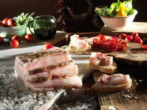 El lardo pata negra sul pane, accanto pomodori freschi ed erbe aromatiche