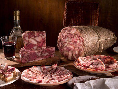 Due piatti di soppressata toscana,due piccole pezze e la grande.accanto un bicchiere di vino rosso