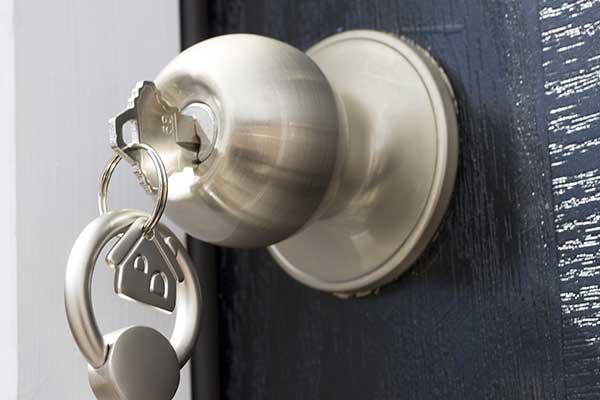 Chiave con un portachiavi a forma di casetta in una serratura di una porta
