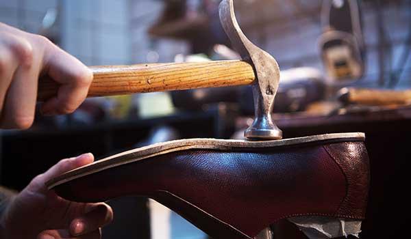 Un uomo con un  martello mentre fissa una suola