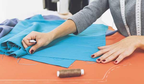 Una donna con un metro di gomma al collo ha le mani appoggiate su una stoffa azzurra