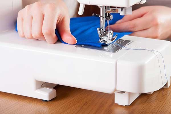 due mani che  usano uja macchina di cucire, stoffa di color blu