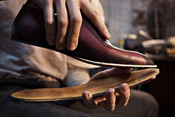 mani di un calzolaio che stanno attaccando la suola a una scarpa di pelle boredeaux