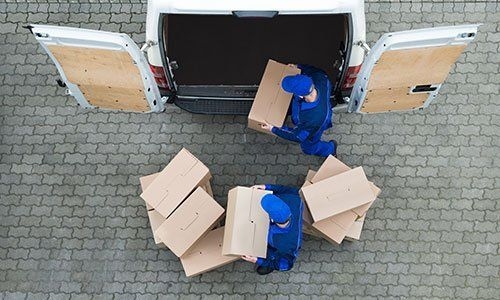 Uomini che scaricano scatole di cartone dal camion