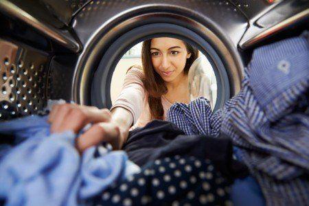 Donna  mettendo la mano nella lavatrice per trarre la biancheria