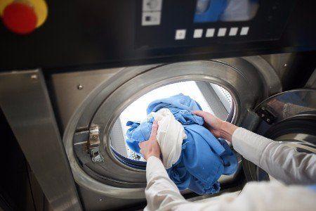 Donna traendo la biancheria della lavatrice