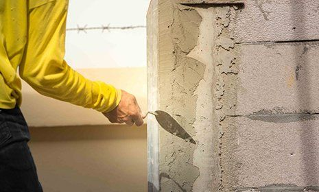 operaio con cazzuola mette il cemento su una parete