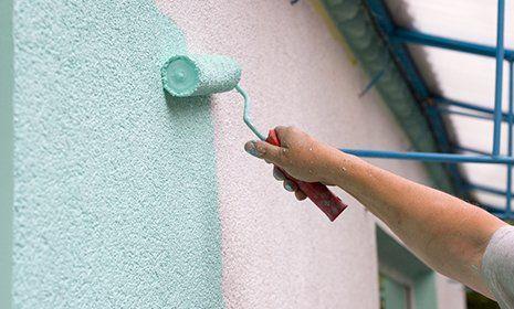 una mano vernicia una facciata di azzurro con un rullo di piccole dimensioni