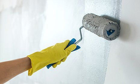 Una mano imbianca una parete in azzurro con un rullo