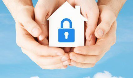 holding a miniature home with lock symbol