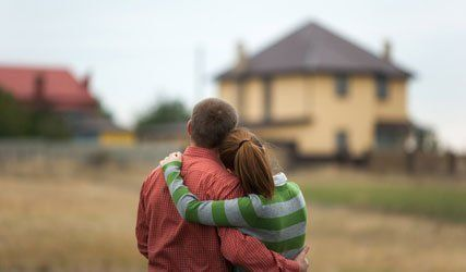 couple in front of a home