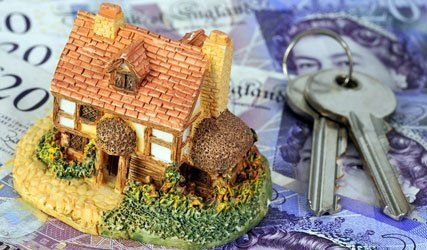 miniature home and keys on a pound note