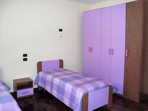 camera viola con due letti singoli e armadio