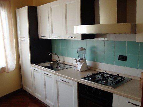 cucina bianca con forno, frullatore e fornello