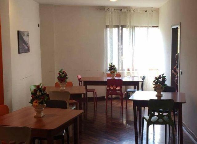 sala pranzo con tavoli, sedie e vasi di fiori