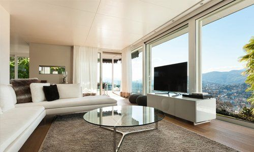 Low white leather sofas facing a flat screen TV against large windows with city view