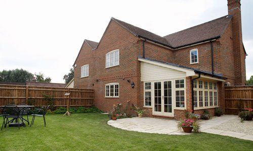 A large red house with cream and glass extension and circular patio leading to a green lawn
