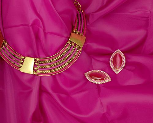 una collana di oro e dei fili di color fucsia e due orecchini in pietra di color fucsia