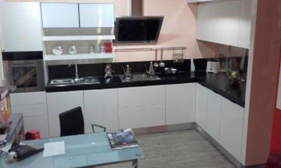 cucina moderna ad angolo bianca con tavolo e sedie