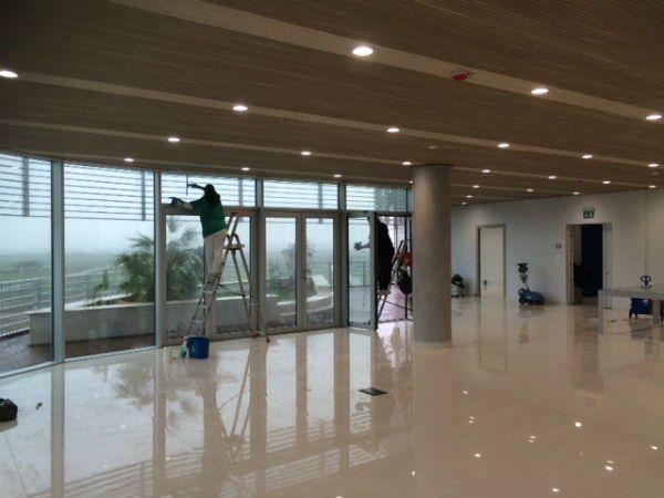 degli inservienti su delle scale che lavano i vetri