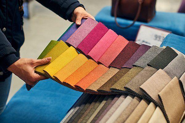 Donna con due campionario di tessuti in diverse gamme di colore