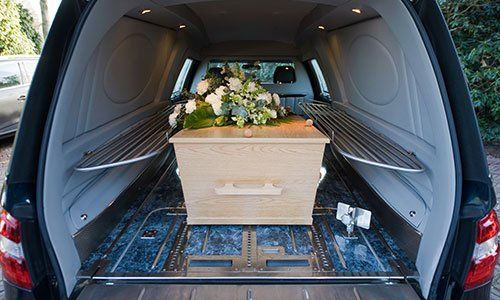 Una bara in una macchina lutto con una composizione floreale