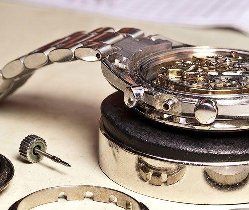 un orologio in acciaio con il coperchio aperto e accanto un ingranaggio