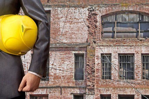 ingegnere con cappello giallo sotto le spalle davanti un edifcio da ristrutturare