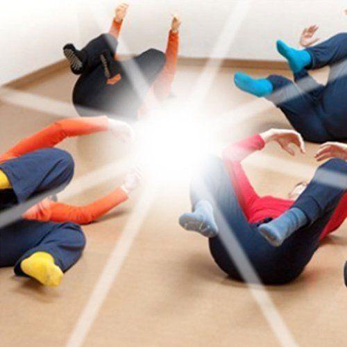 delle persone sdraiate a terra in posizioni di yoga e in mezzo una luce intensa