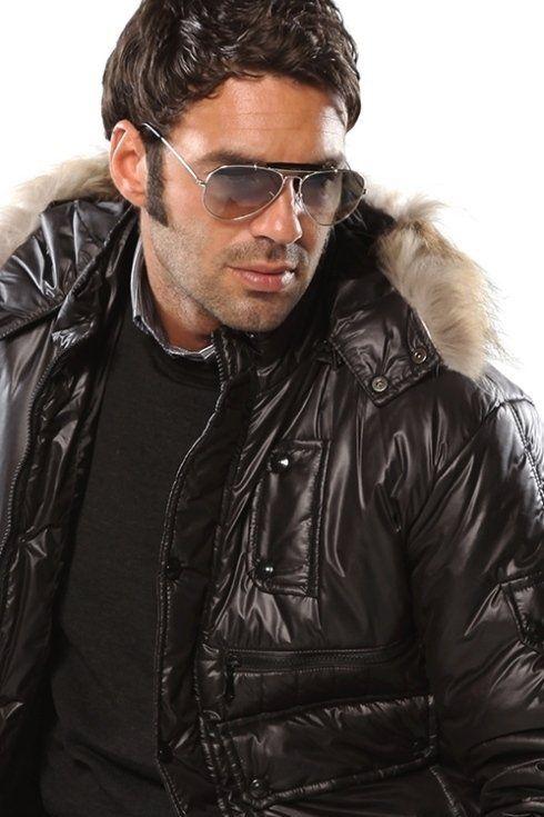 un uomo vestito giacca con occhiali da sole mentre posa per un foto