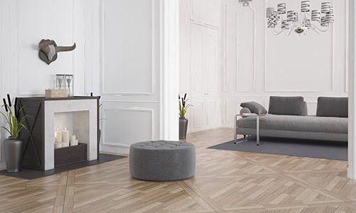 salotto moderno con divano e puff grigio scuro e sulla sinistra un mobile bianco e grigio con sopra degli oggetti e sotto delle candele bianche accese