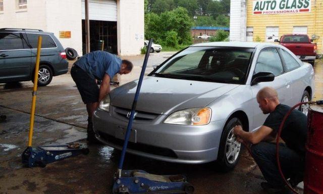 Mechanics checking tire pressure