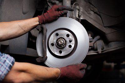 meccanico incastra una ruota di metallo in un auto