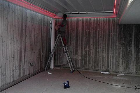 operaio  su scala mentre costruisce tettoia