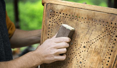 Mani rimuovono la vernice da una sedia con la carta vetrata a Napoli
