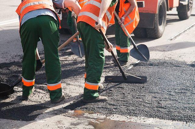 delle persone che asfaltano una strada