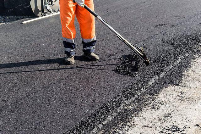 un uomo con una pala durante un'opera di asfaltazione