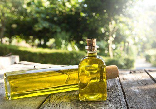 bottiglie di olio extra vergine di oliva su fondo in legno